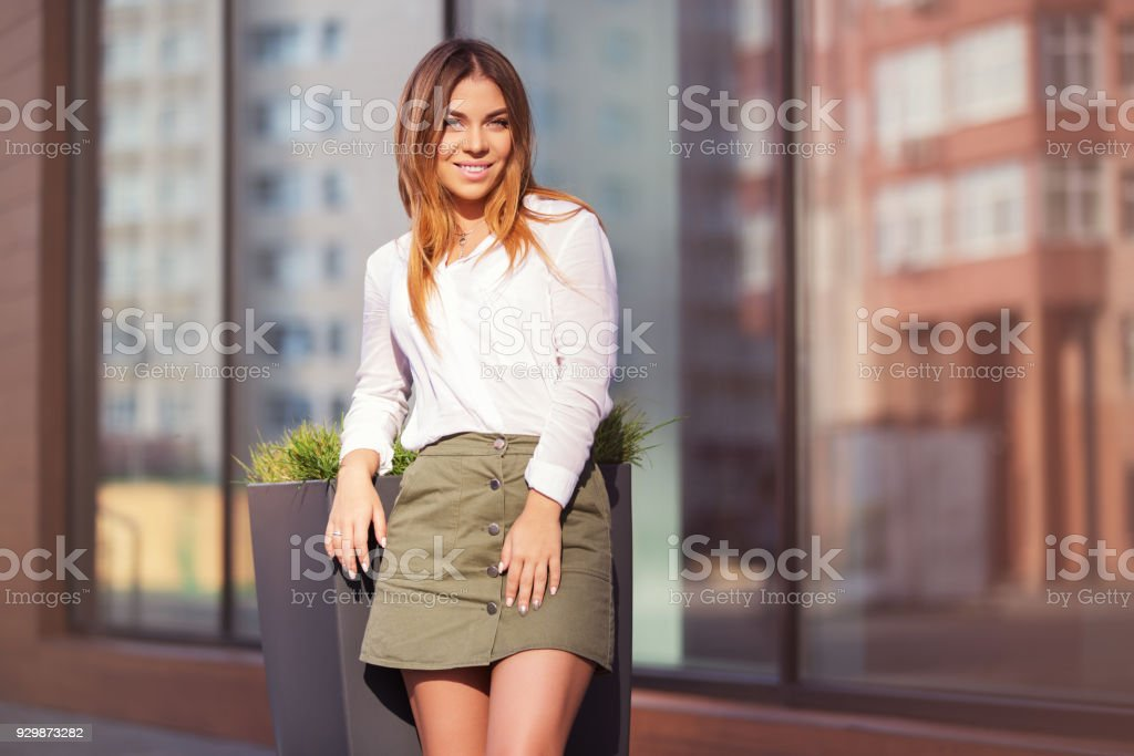 Young fashion woman in white shirt and short skirt in a city street stock photo