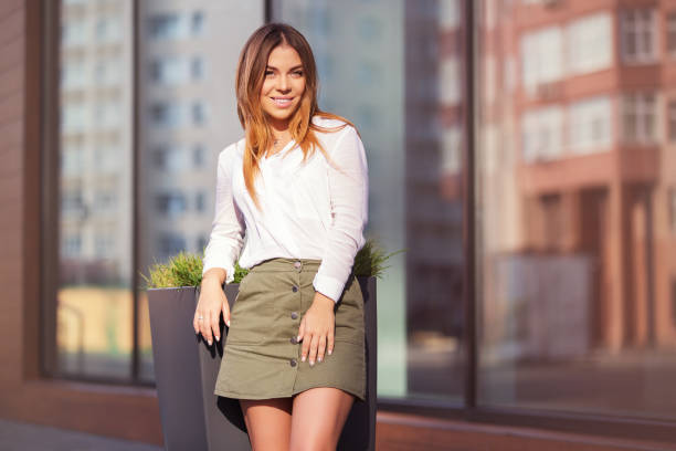 Young fashion woman in white shirt and short skirt in a city street