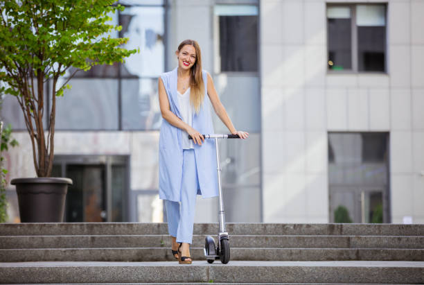 Young fashion woman with scooter downtown stock photo