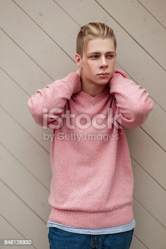 846124694 istock photo Young fashionable blond man with a hairstyle in a pink sweater near a wooden wall 846126930