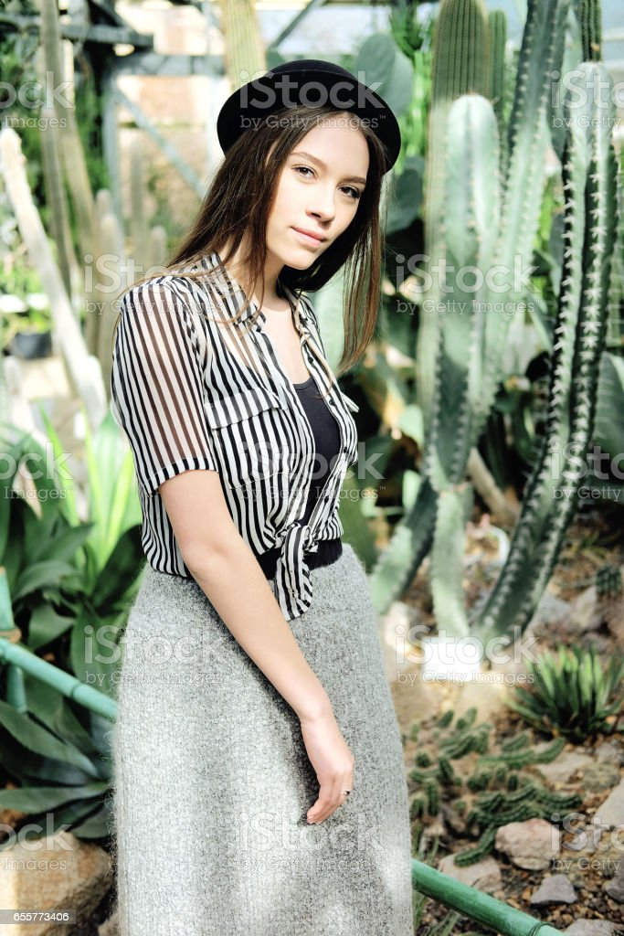 Young fashionable caucasian woman with long hair wearing hat and striped blouse basking in sunlight inside greenhouse near agave and cactus plants stock photo