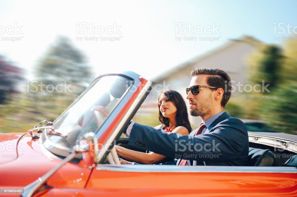 Young fashionable couple in an oldtimer convertible sportscar stock photo