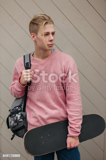 846124660istockphoto Young fashionable handsome man with a backpack and skateboard on the beach near a wooden wall 846126866