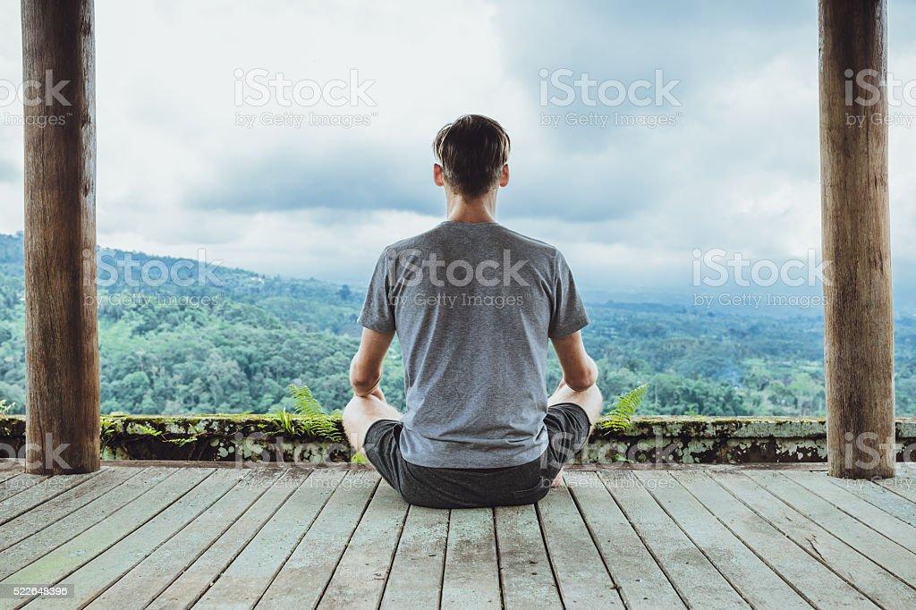 Young fashionable man meditating in the gazebo stock photo