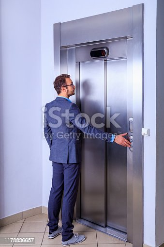 638591126 istock photo Young fashionable professional in suit waiting in front of the elevator 1178836657