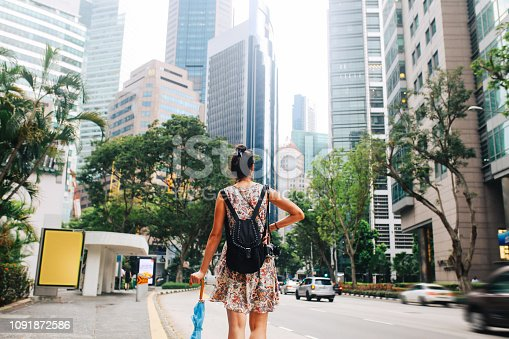 Vintage toned street style portrait of a young fashionable brunette woman, walking in Singapore downtown district. She is wearing a summertime dress, walking on the busy streets beneath the Singapore skyscrapers.