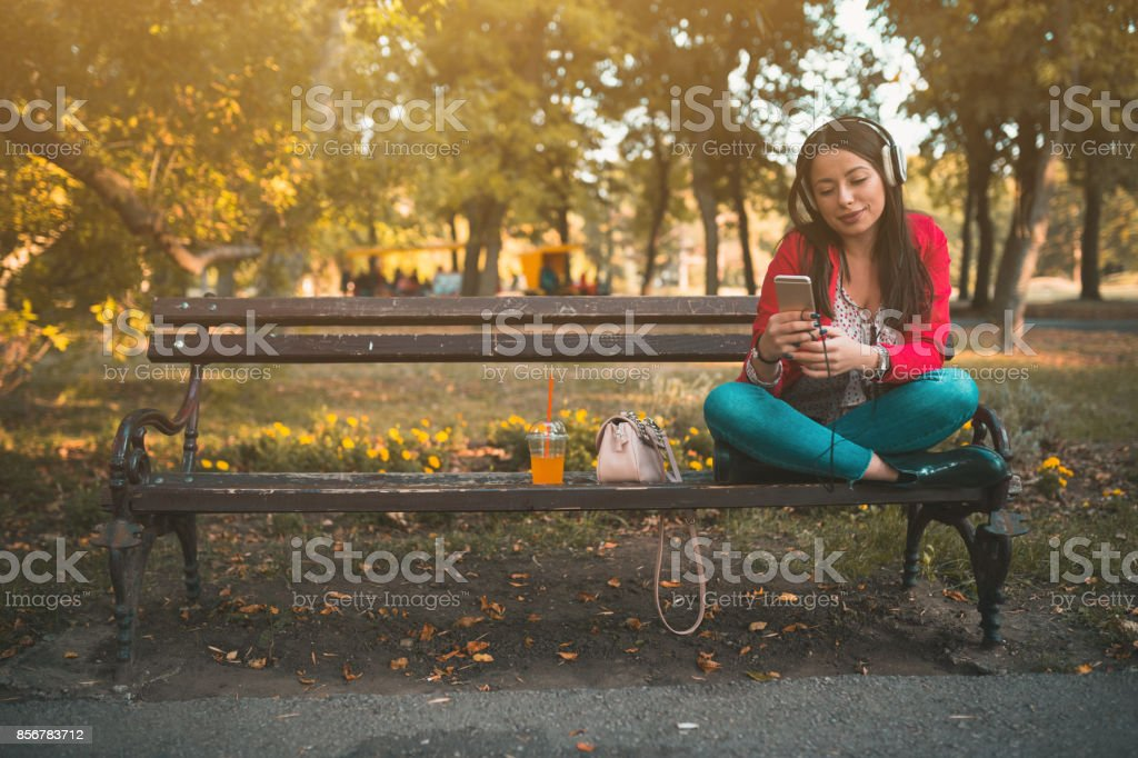 Young fashionable woman listening to music in the park stock photo