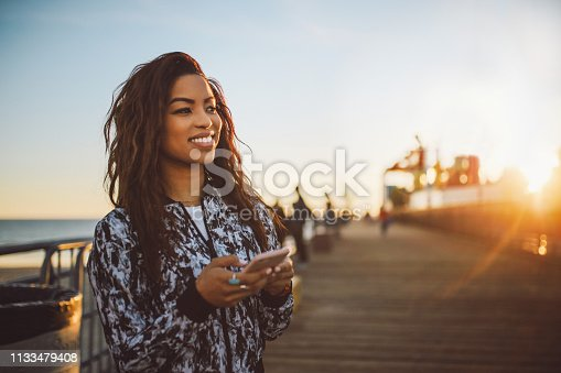 Natural light portrait of a beautiful, fashionable mixed race Latina, walking between Santa Monica and Venice beach in Los Angeles, California. She is just chilling, texting on social networks while meeting her friends, enjoying the nice summertime weather in California.