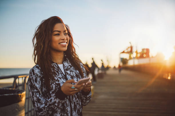 young fashionable woman texting on her phone in Santa Monica, LA stock photo