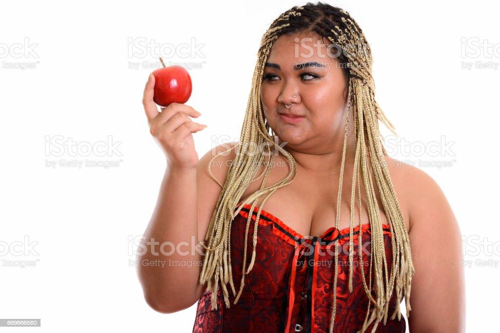 年輕胖的亞洲女人抱著,看著紅紅的蘋果圖像檔