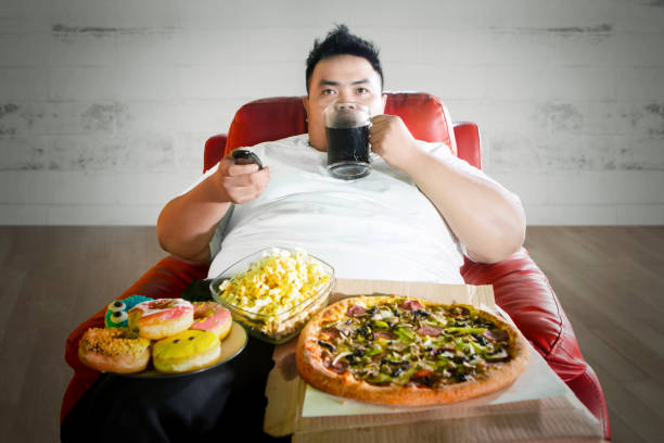 Young fat man enjoying junk foods on the sofa stock photo