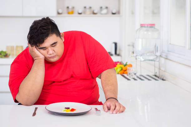 Joven gordo parece aburrido para comer ensalada - foto de stock