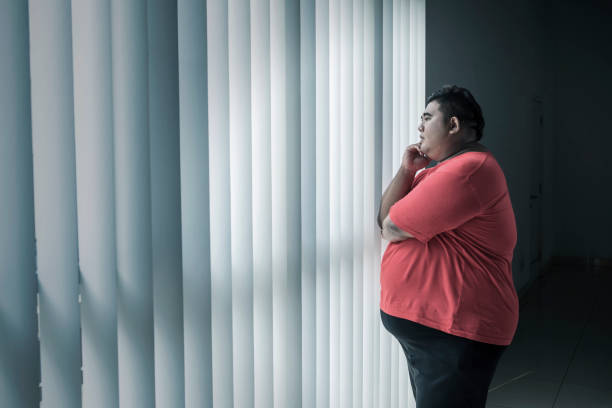 Young fat man thinking something near the window