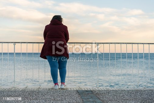 Young fat woman standing alone on the beach of the Mediterranean Sea in Antalya