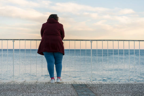 Young fat woman standing alone on the beach stock photo