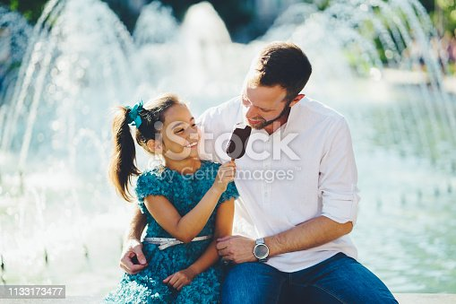 Little girl in the park giving ice-cream to hеr father