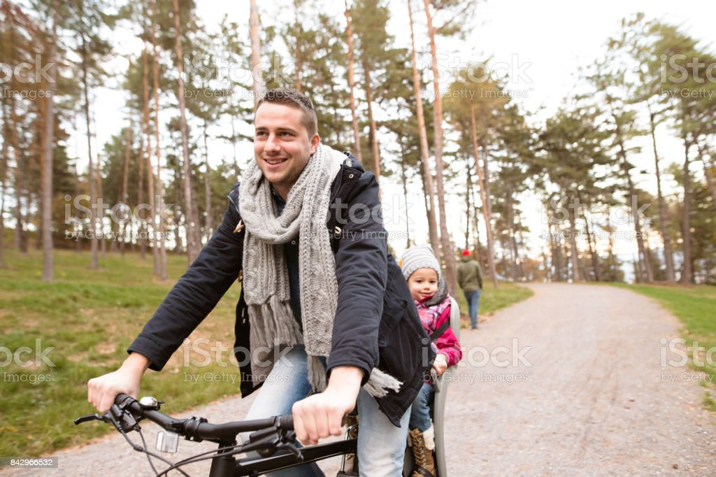 Young father and daughter together on bicycle in autumn park stock photo