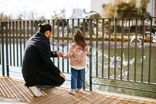 Happy young father and his adorable toddler daughter feeding seagull on a river in a spring park