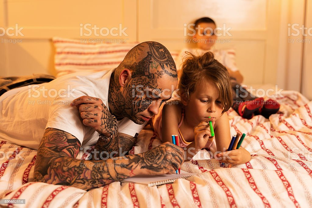 Young father and his daughter drawing in the bedroom. stock photo