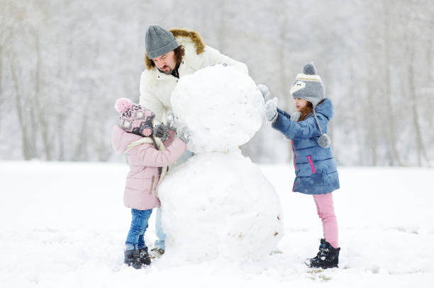 Young father and his daughters building a snowman stock photo
