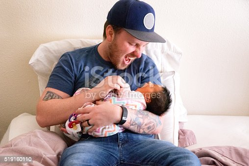 Poignant and authentic, heartfelt moment of a young father in his 20s holding, bonding and interacting with his beautiful newborn baby girl.