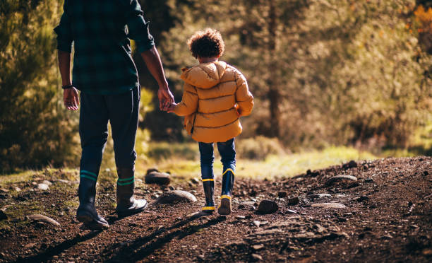 Young father and son with rain boots walking in nature stock photo