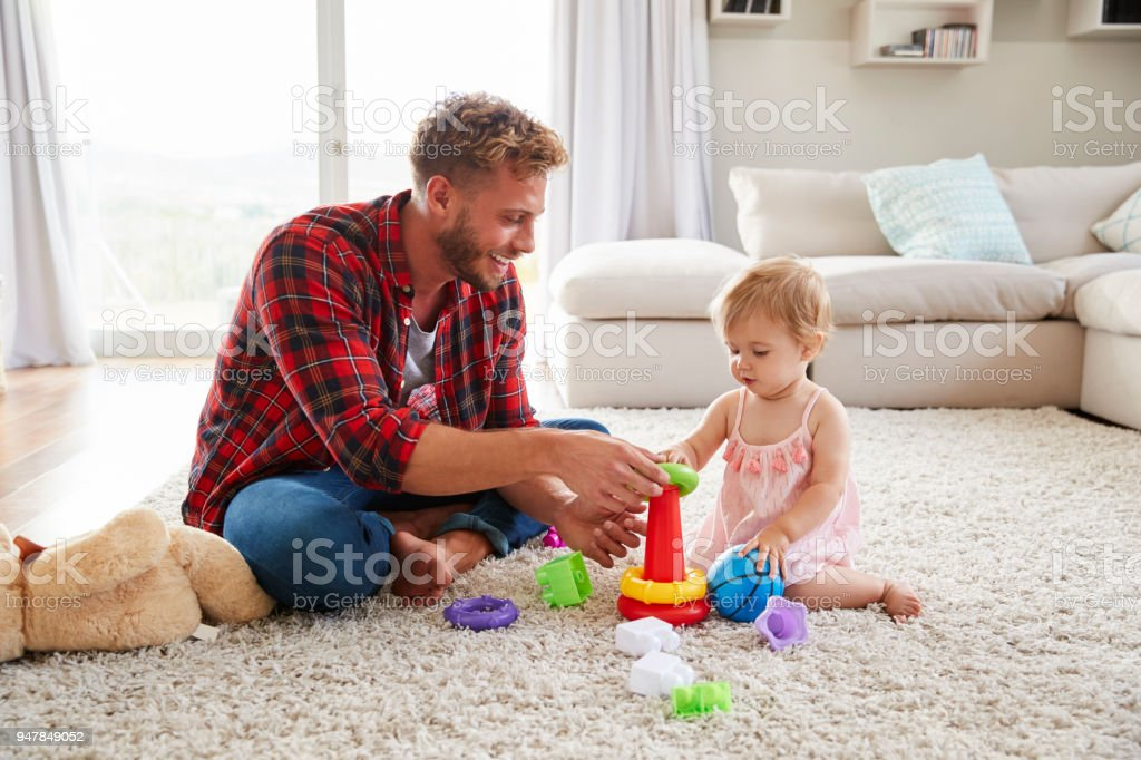 Young father and toddler daughter playing in sitting room stock photo