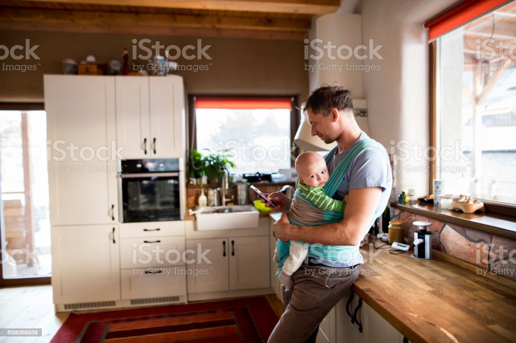Young father at home in the kitchen holding smart phone, texting, baby son in sling stock photo