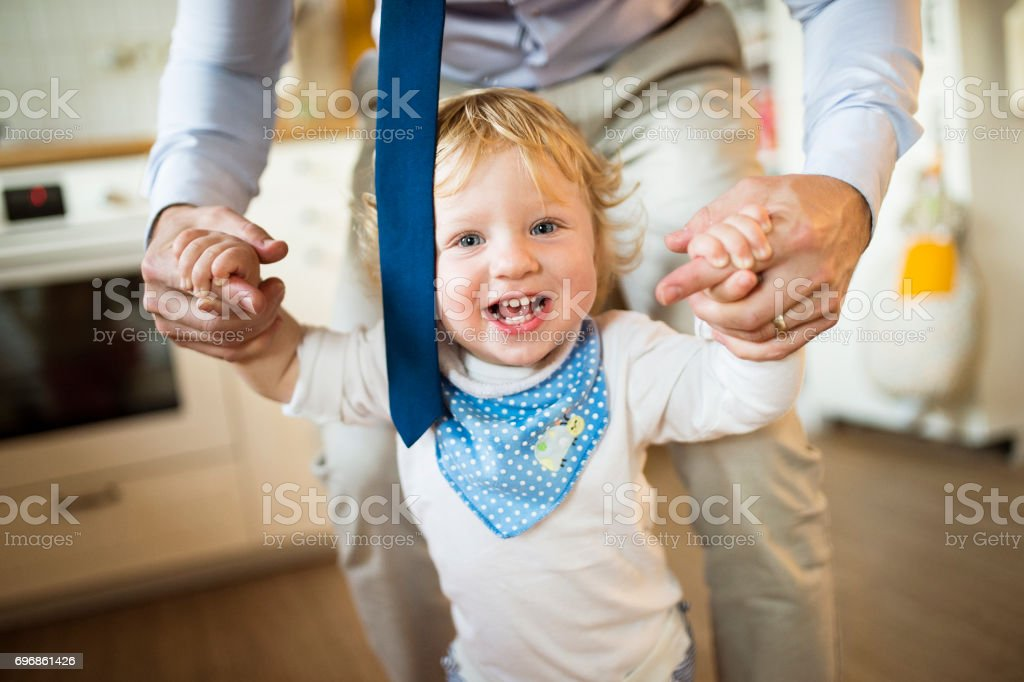 Young father at home with his son. stock photo