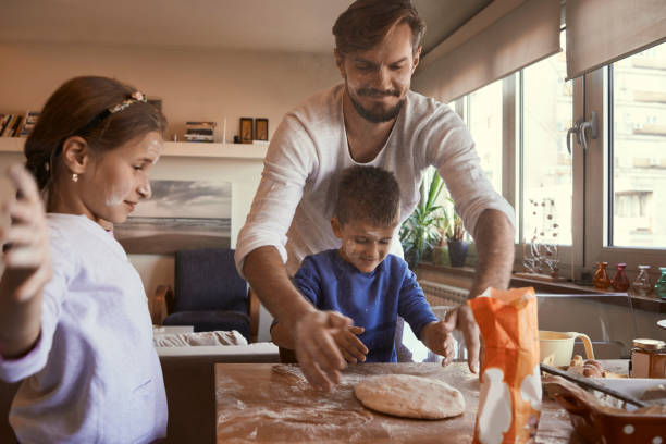 young father baking with his children family having fun baking together baking bread stock pictures, royalty-free photos & images