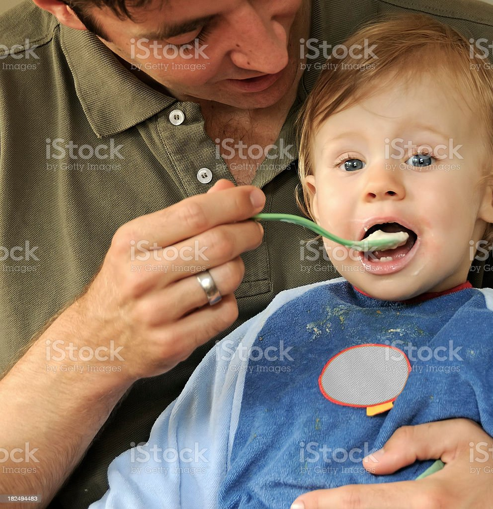 Young father caring feeding one-year-old eating child spoon mouth royalty-free stock photo