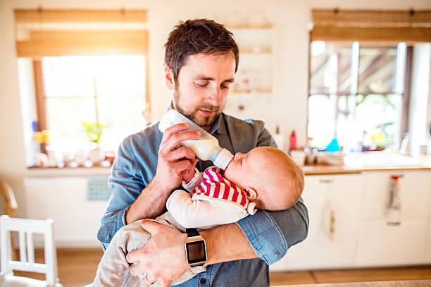 Junge, die Fütterung von Vater und sein Neugeborenes baby Sohn – Foto