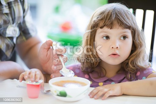 istock Young father feeding his little girl, fatherhood 1056392502