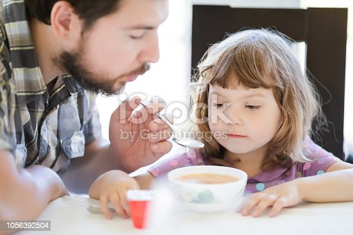 istock Young father feeding his little girl, fatherhood 1056392504