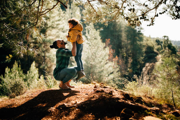 Young father having fun lifting son up under forest tree stock photo