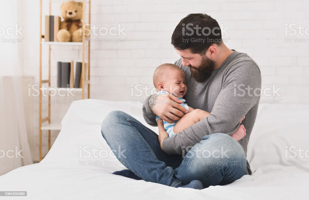 Young father holding crying sleepy cute newborn baby stock photo