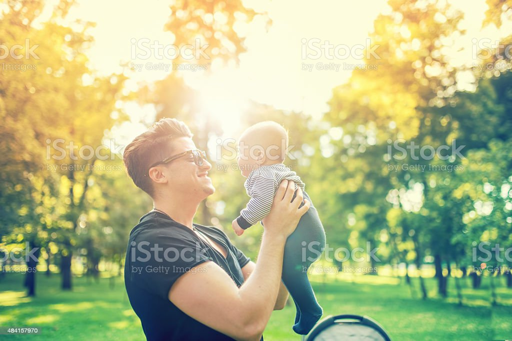 Young father holding delicate newborn infant in arms outdoor stock photo