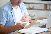 istock Young father holding newborn child and using mobile phone 593329378