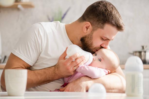 jeune père embrassent son bébé pendant le lait de consommation - père photos et images de collection