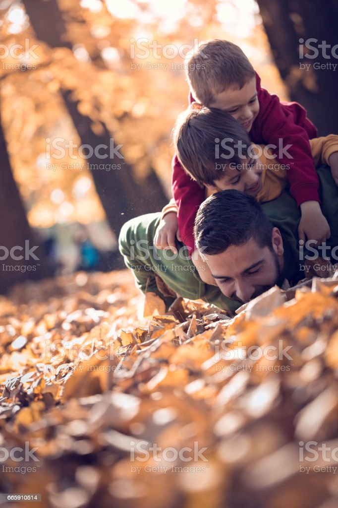 Young father lying on autumn leaves and holding two sons on his back in park foto stock royalty-free