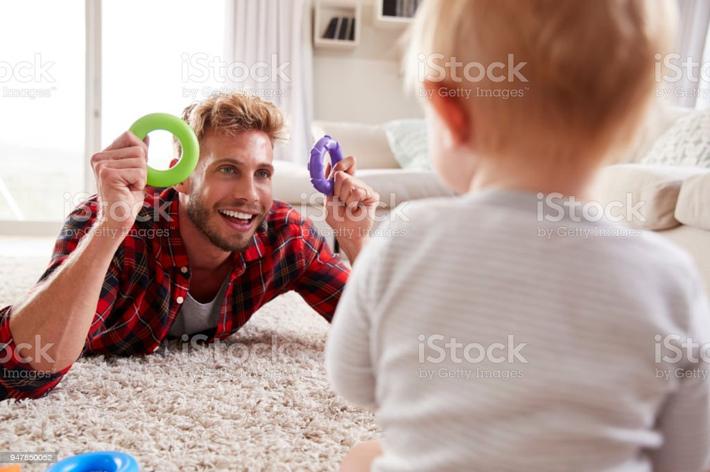 Young father lying on floor playing with toddler son at home stock photo