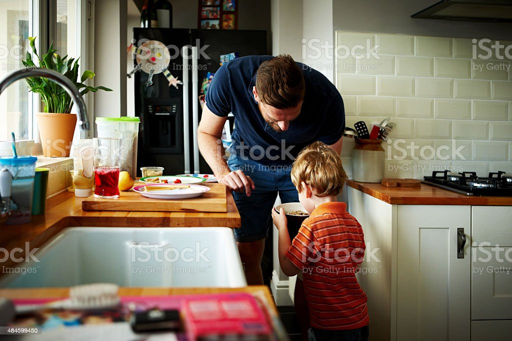 Young father making breakfast for his son stock photo