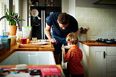 Young father making breakfast for his son
