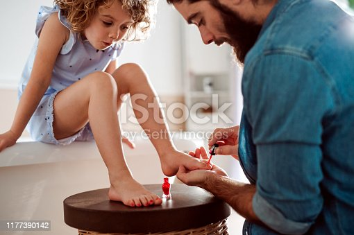 A young father painting small daughter's nails in a bathroom at home.
