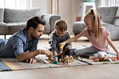 Loving young father lying on floor with little kids play with building bricks toys together, caring dad have fun enjoy family weekend with small children engaged in funny childish activity at home