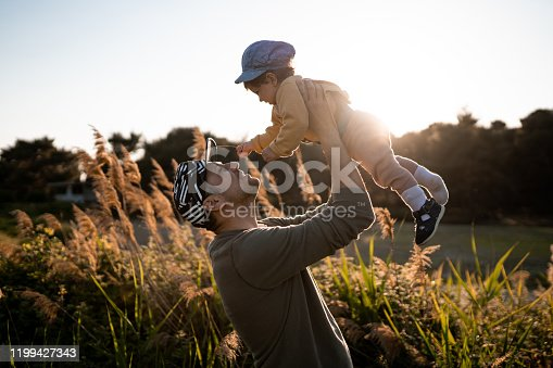 Young father playing with his daughter on sunny day