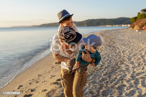 Young father playing with kids on beach