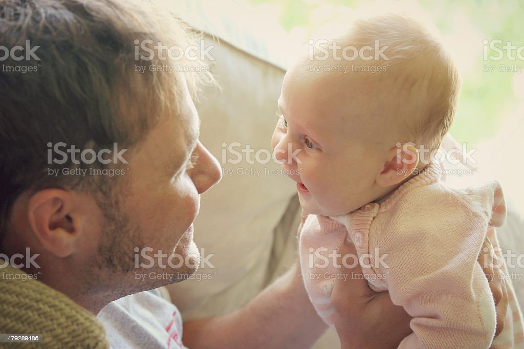 Young Father Playing with Newborn Baby Girl stock photo