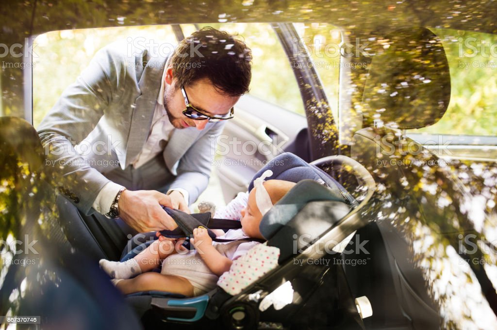 Young father putting baby girl in the car. stock photo