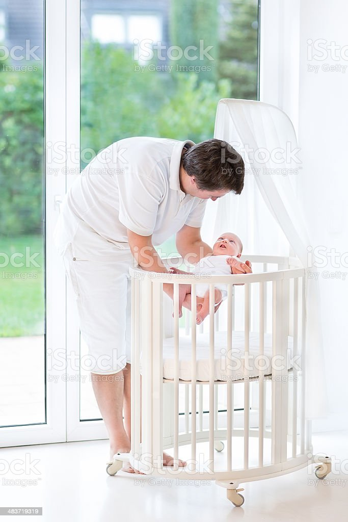 Young father putting his smiling newborn baby into round crib royalty-free stock photo